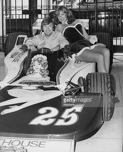 Racing driver Guy Edwards of Great Britain sits aboard the Penthouse Rizla Racing Hesketh 308D Ford Cosworth DFV V8 whilst model Suzanne Turner whose...