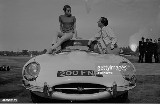 Racing driver Innes Ireland and Kathy Keeton posing with a Jaguar EType September 13th 1964