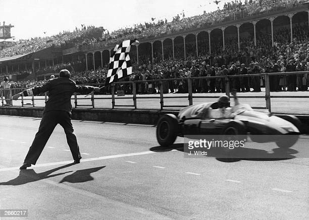Racing driver Jack Brabham takes the checkered flag in his CooperClimax to win the British Grand Prix at Aintree18th July 1959