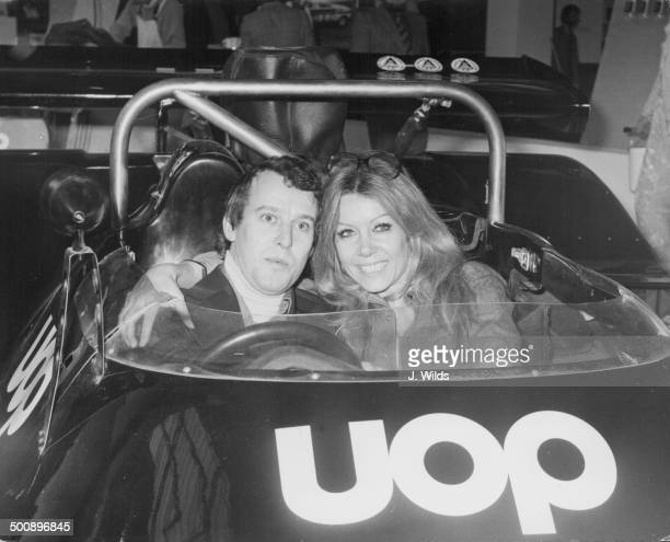 Racing driver Jackie Oliver and actress Ingrid Pitt sitting inside a UOP CanAm car together at the Speedshow 1975 Olympia London January 2nd 1975