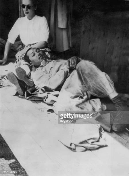 Racing driver Prince Bira of Siam relaxes with his wife Ceril before the start of the Swiss Grand Prix at Berne 10th June 1947