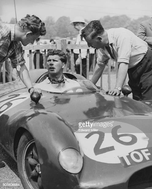 Racing driver Tim Parnell sitting at the wheel of his car as he talks to two mechanics at the start of the August Trophy Race at Crystal Palace...