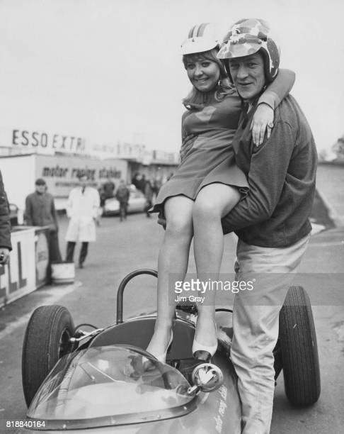 Racing driver Tony Lanfranchi lifts Scottish singer Lulu into a singleseater racing car at Brands Hatch UK after she failed her driving test 3rd...