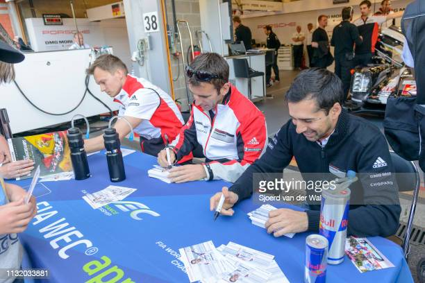 Racing drivers Romain Dumas Neel Jani and Marc Lieb signing cards during the pitwalk before the race in front of the Porsche pit box with the Porsche...
