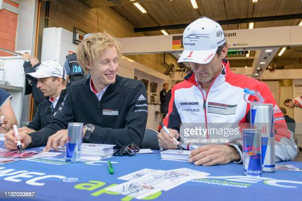 Racing drivers Timo Bernhard Brendon Hartley and Mark Webber signing cards during the pitwalk before the race in front of the Porsche pit box with...