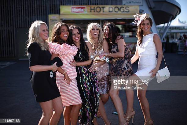 Racing fans soak up the sunshine and dress to impress during Ladies Day at the Aintree Grand National meeting on April 8 2011 in Aintree England...