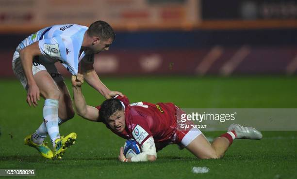 Racing fly half Finn Russell gets to grips with Scarlets wing Steffan Evans during the Champions Cup match between Scarlets and Racing 92 at Parc y...