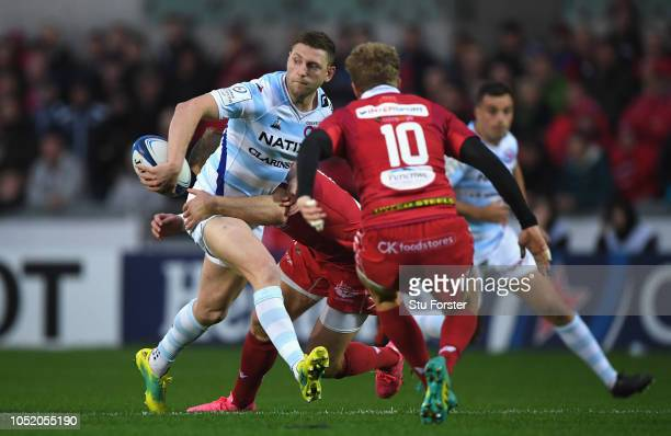 Racing fly half Finn Russell offloads in the tackle of Hadleigh Parkes during the Champions Cup match between Scarlets and Racing 92 at Parc y...