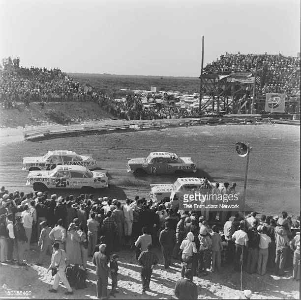 Racing happens in close proximity to spectators and journalists Two Plymouths and two Fords kicking up sand in the grandstand turn Curtis Turner in...