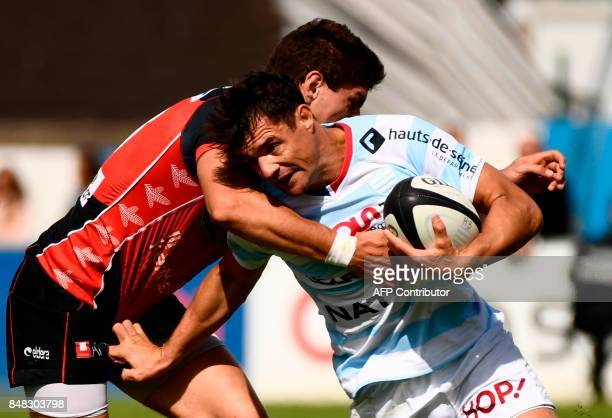 Racing Metro 92 New Zealand fly-half Dan Carter is tackled by Oyonnax's flanker Curtis Browning during the TOP14 rugby union match Racing 92 against...