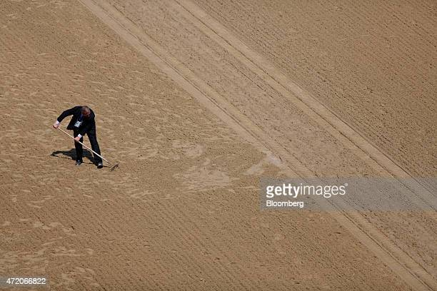 A racing official smooths out the track before a race on the running of the 141st Kentucky Derby at Churchill Downs in Louisville Kentucky US on...