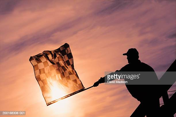 Racing official waving checkered flag at finish line