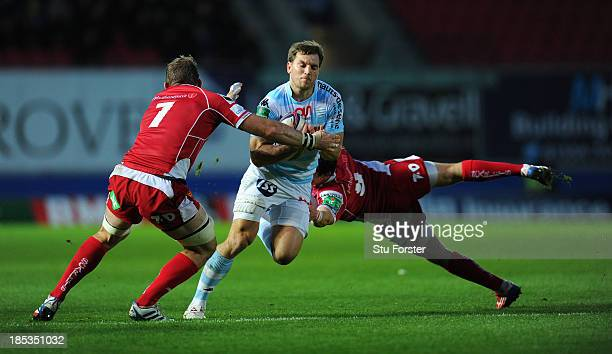 Racing player Adrien Plante runs into Scarlets players John Barclay and Rhodri Williams during the Heineken Cup Pool 4 match between Scarlets and...