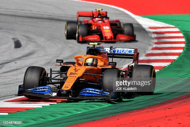 Racing Point's Canadian driver Lance Stroll steers his car in front of Ferrari's Monegasque driver Charles Leclerc during the Austrian Formula One...
