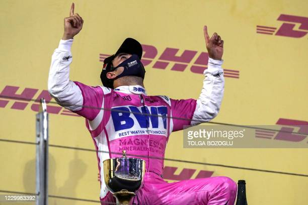 Racing Point's Mexican driver Sergio Perez celebrates on the podium after winning the Sakhir Formula One Grand Prix at the Bahrain International...