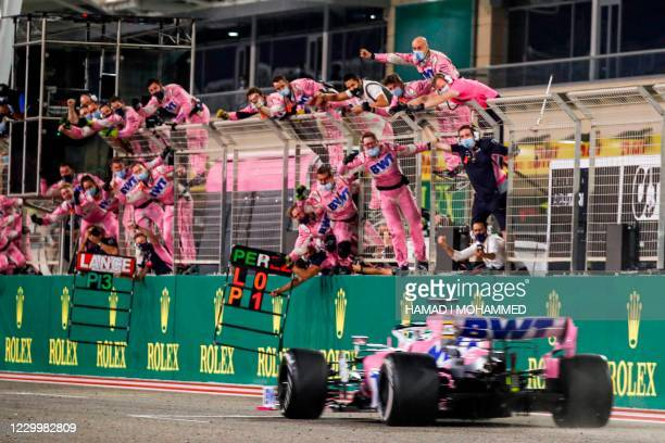 Racing Point's Mexican driver Sergio Perez is cheered by his team after winning the Sakhir Formula One Grand Prix at the Bahrain International...