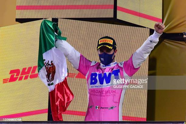 Racing Point's Mexican driver Sergio Perez waves the Mexican flag on the podium after winning the Sakhir Formula One Grand Prix at the Bahrain...