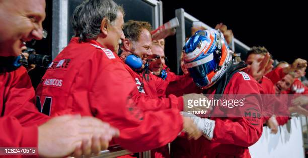 racing team celebrating victory - racing driver stock pictures, royalty-free photos & images