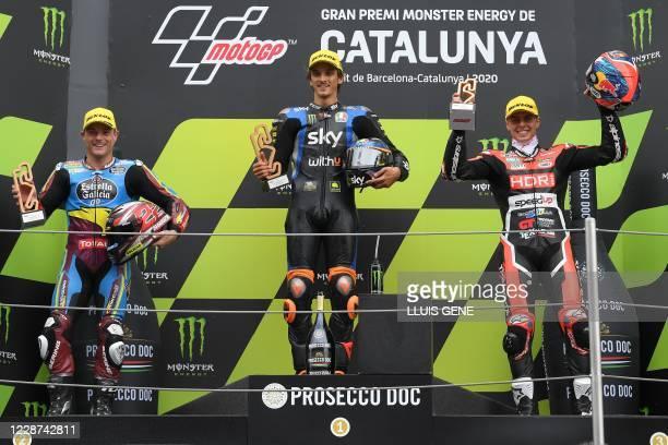 Racing Team VR46's Italian rider Luca Marini celebrates his victory on the podium with Federal Oil Gresini's British rider Sam Lowes and Beta Tools...