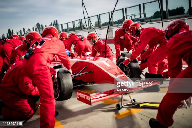 racing team working at pit stop - race car driver stock pictures, royalty-free photos & images