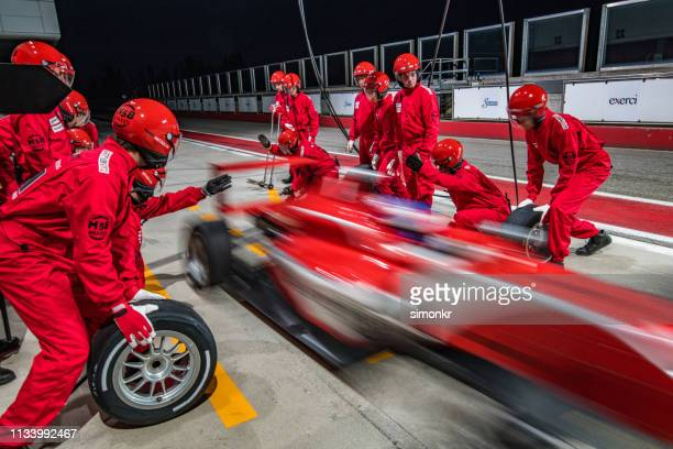 racing team working at pit stop - change stock pictures, royalty-free photos & images