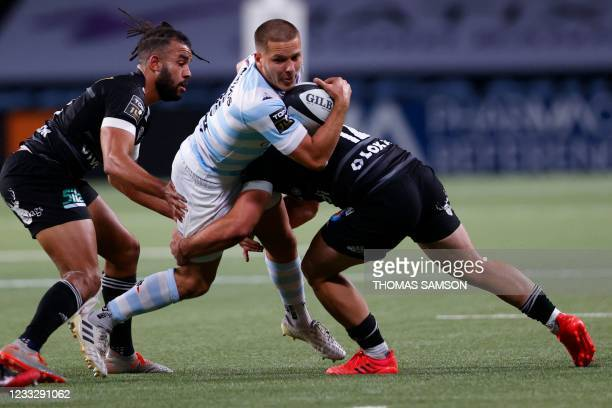 Racing92's French fly-half Antoine Givert is tackled by Brive's French centre Guillaume Galletier during the French Top14 rugby union match between...