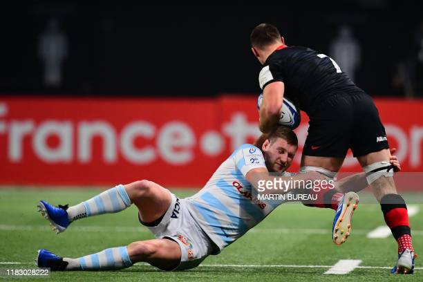 Racing92's Scottish flyhalf Finn Russell tackles Saracens' English flanker Ben Earl during the European Champions Cup rugby union Pool 4 match...