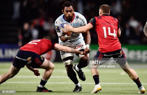 Racings Fidjian number 8 Leone Nakarawa is tackled by Munster's Irish center Rory Scannell and Irish winger Andrew Conway during the European...