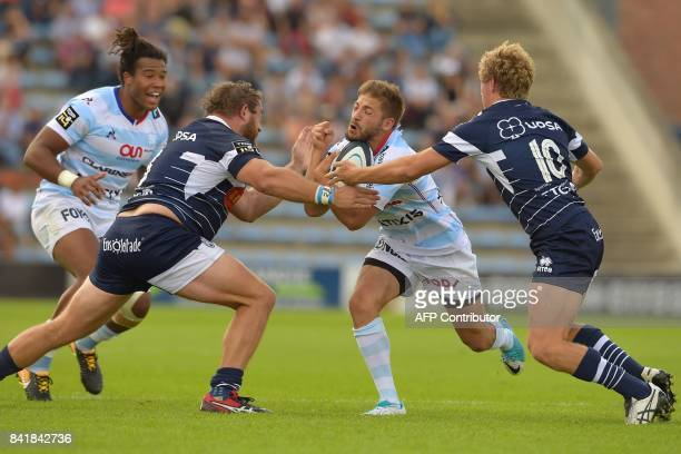 Racing's French scrumhalf Teddy Iribaren is tackled by Agen's Irish prop Dave Ryan and Agen's Australian flyhalf Jake McIntyre as Racing's French...