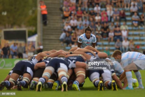 Racing's French wing Teddy Thomas looks at players engaging a scrum during the French Top 14 rugby union match between Agen and Racing 92 on...