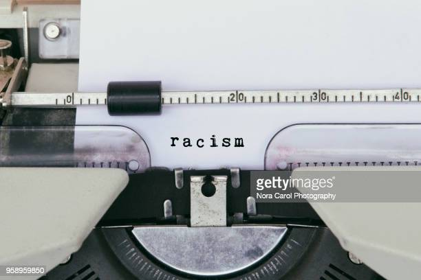 racism typed on vintage typewriter - prejudice stock pictures, royalty-free photos & images