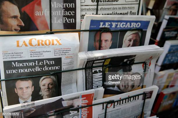 A rack displays newspapers front pages with pictures of French Presidential election candidates Emmanuel Macron and Marine Le Pen a day after the...