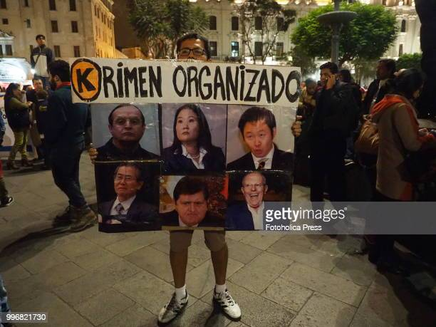 Racketeering poster with Peruvian last presidents and main politics pictures held by a man when citizens take to the streets of Lima and occupy the...