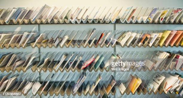 racks of brochures on shelves - mail stock pictures, royalty-free photos & images