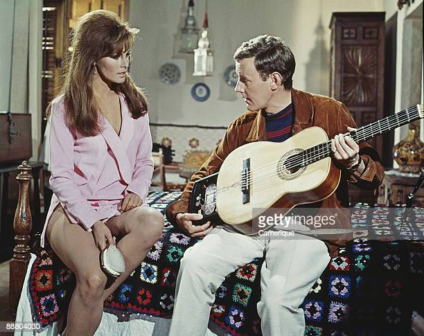 Racquel Welch listens to Richard Briers playing the guitar in this scene from the movie 'Fathom' 1967