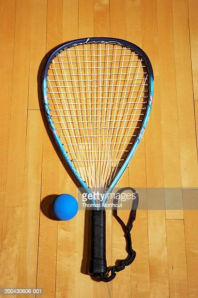 Racquetball and racket on hardwood floor of racquetball court
