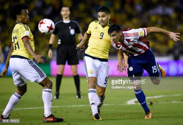 Radamel Falcao and Juan Cuadrad of Colombia struggles for the ball with Fabian Balbuena of Paraguay during a match between Colombia and Paraguay as...
