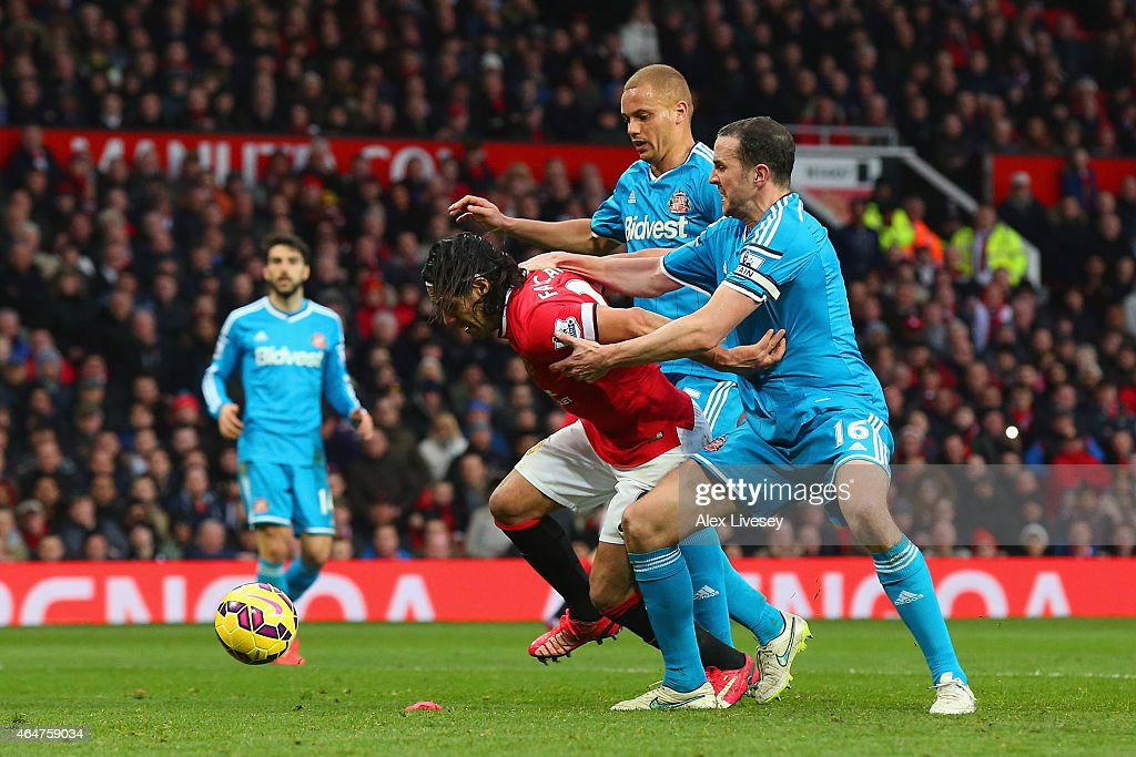Radamel Falcao García of Manchester United is brought down in the area by Wes Brown and John O'Shea of Sunderland to win a penalty during the Barclays Premier League match between Manchester United and Sunderland at Old Trafford on February 28, 2015 in Manchester, England.