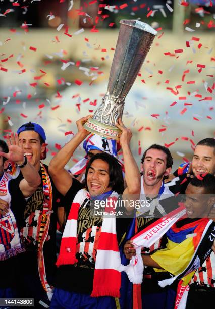 Radamel Falcao of Atletico Madrid holds up the Europa League trophy while celebrating with fans at Plaza Neptuno a day after Atletico won the Europa...