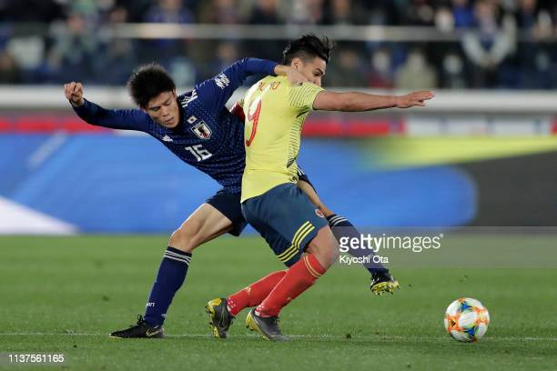 Radamel Falcao of Colombia and Takehiro Tomiyasu of Japan in action during the international friendly match between Japan and Colombia at Nissan...