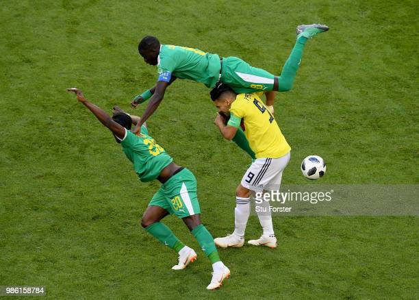 Radamel Falcao of Colombia is tackled by Cheikhou Kouyate and Keita Balde of Senegal during the 2018 FIFA World Cup Russia group H match between...