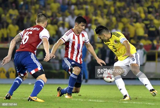 Radamel Falcao of Colombia vies for the ball with Robert Piris and Fabian Balbuena of Paraguay during a match between Colombia and Paraguay as part...