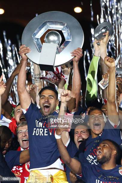 Radamel Falcao of Monaco holds the trophy between President of AS Monaco Dmitri Rybolovlev and Kylian Mbappe during the French League 1 Championship...