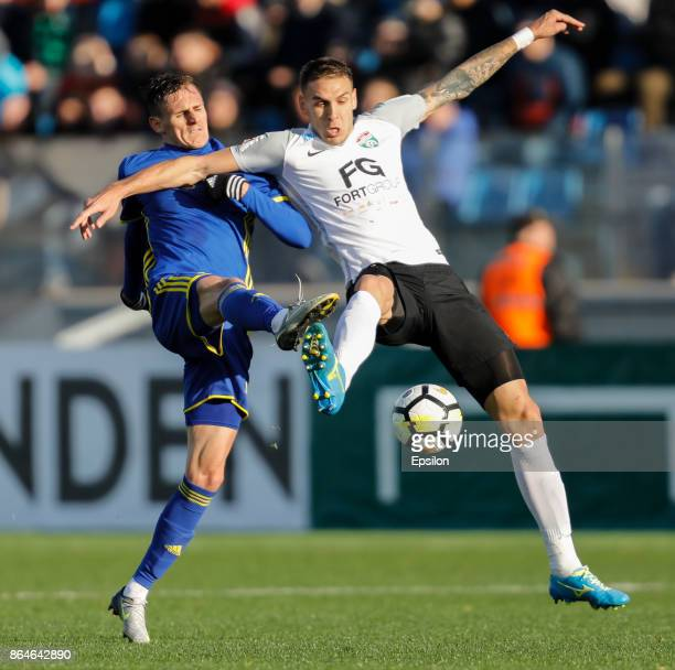Rade Dugalic of FC Tosno and Vladimir Dyadyun of FC Rostov vie for the ball during the Russian Football League match between FC Tosno and FC Rostov...