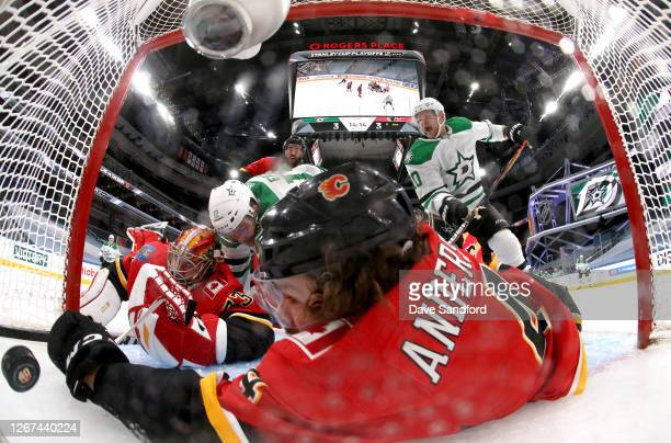 Radek Faksa of the Dallas Stars falls into goaltender Cam Talbot of the Calgary Flames as Rasmus Andersson reaches to try and stop the puckafter...