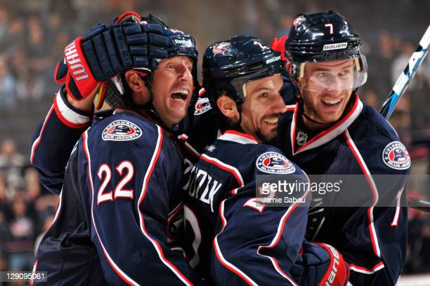 Radek Martinek of the Columbus Blue Jackets is congratulated by teammates Vinny Prospal and Jeff Carter after scoring against the Colorado Avalanche...