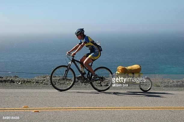 Radfahrer bei einer Radtour auf dem Highway 1 in Kalifornien Fahrrad mit Gepäckanhänger