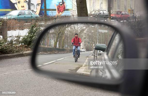 Radfahrer im Rückspiegel eines Autos