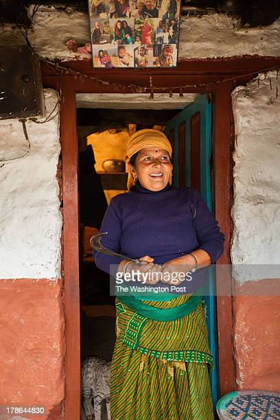 Radhika Subedi or Aamaa as she is affectionately known stands in the doorway of her house It is Nepali tradition to place photos of older or passed...