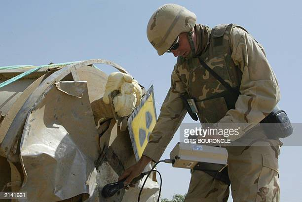 Radiation expert checks the radio active levels on a mixing vat allegedly stolen by looters and dumped outside the grounds of the Tuwaitha nuclear...